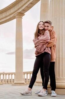 Giovani coppie amorose felici che si abbracciano all'aperto nel parco divertendosi