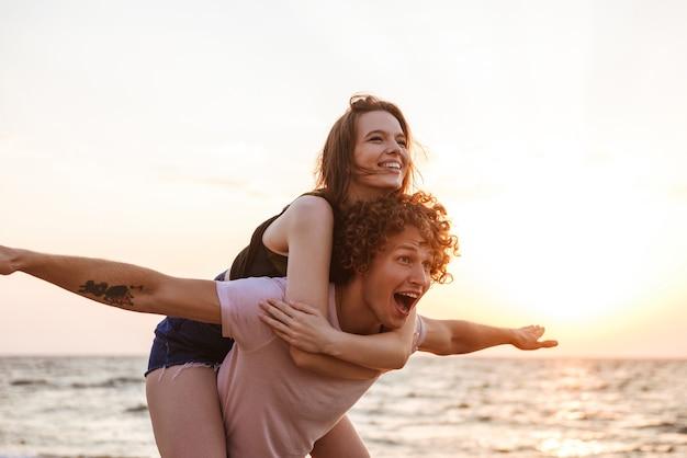 Felice giovane coppia di innamorati divertendosi all'aperto sulla spiaggia