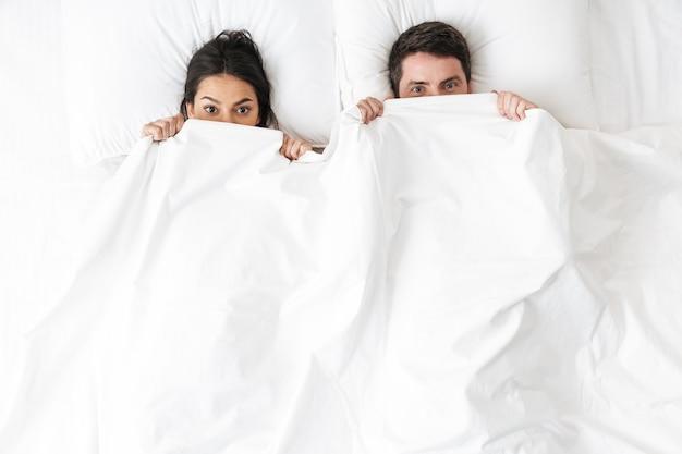 Una giovane coppia di innamorati felice giace a letto nascondendosi sotto la coperta