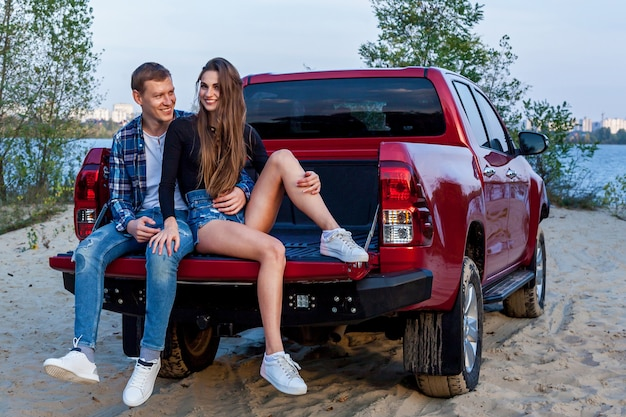 Felice giovane coppia amorosa sorridente e abbracciata nella parte posteriore di un'auto rossa sulla spiaggia vicino al lago. abbracci di giovane coppia vicino alla macchina.
