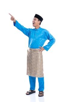 Giovane maschio felice della malesia che osserva in su che indica il copyspace