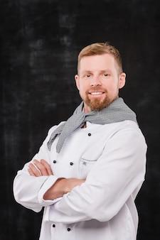 Felice giovane chef maschio in uniforme ti guarda mentre in piedi su sfondo nero in isolamento