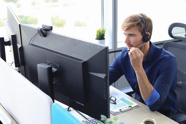 Felice giovane dirigente maschio del supporto clienti che lavora in ufficio.