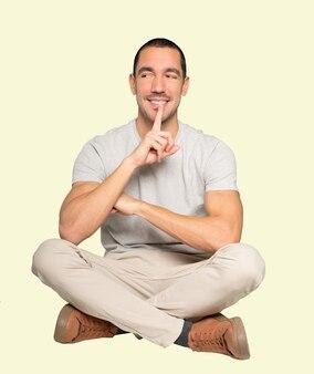 Felice giovane uomo che chiede silenzio gesticolando con il dito