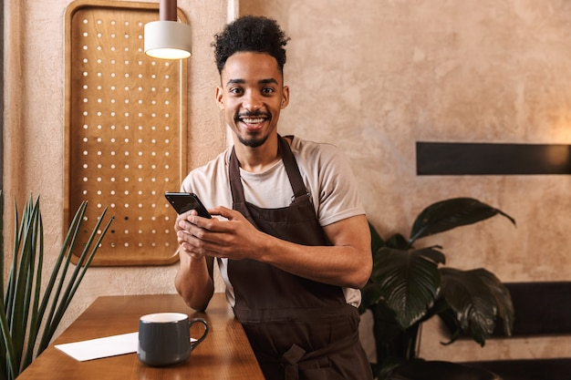 Felice giovane barista che indossa un grembiule in piedi presso la caffetteria, utilizzando il telefono cellulare