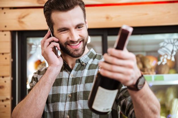 Giovane felice che compra vino e parla al cellulare nel negozio di alimentari