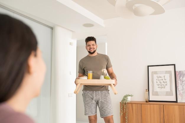 Giovane felice che porta il vassoio con la colazione per sua moglie