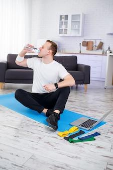 Il giovane felice beve l'acqua dopo l'allenamento online. fare sport in casa, stile di vita sano