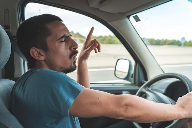 Giovane felice che guida un'auto balla e canta trasporto di viaggio divertente e concetto di veicolo