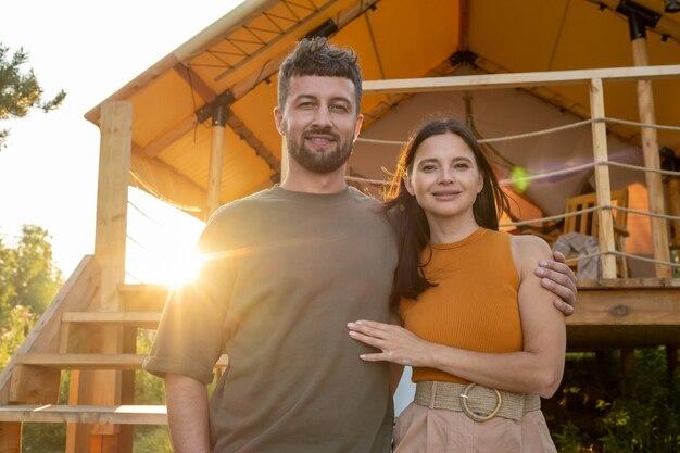 Felice giovane che abbraccia sua moglie contro la tenda glamping