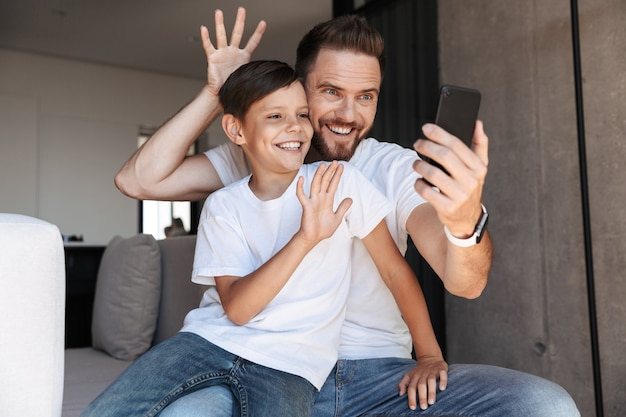 Felice giovane padre papà utilizzando il telefono cellulare con suo figlio