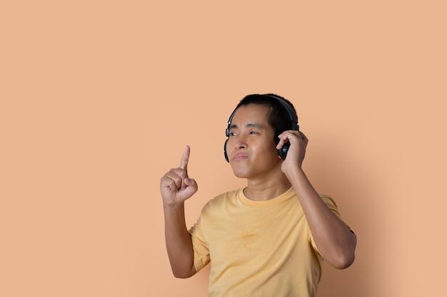 Felice giovane in cuffie che ascolta la musica e balla su sfondo arancione studio. ascoltare musica.