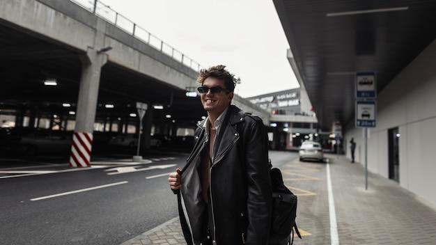 Felice giovane hipster con un sorriso divertente in una giacca di pelle nera alla moda con un'acconciatura alla moda e sorridente in una strada della città. modello di ragazzo alla moda gioioso in occhiali da sole all'aperto.
