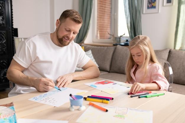 Felice giovane uomo e la sua piccola figlia carina seduti da un tavolo di legno in soggiorno e disegno con evidenziatori su carta