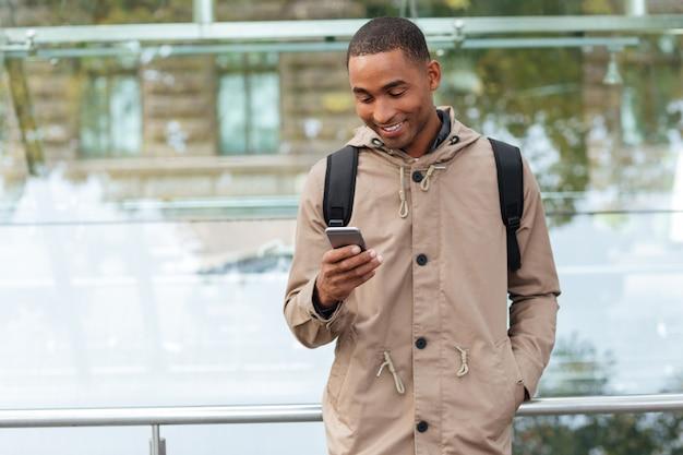 Felice giovane uomo che tiene il suo cellulare in mano e in chat