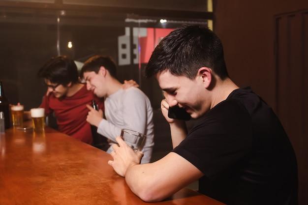 Un giovane felice che ride mentre parla al telefono mentre i suoi amici ubriachi si godono una birra al bar.