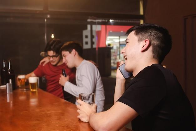 Un giovane felice che ride mentre parla al telefono mentre i suoi amici si godono una birra al bar.