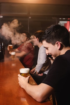 Un giovane felice che ride mentre parla al telefono mentre i suoi amici si godono una birra e si svapano al bar - scatto verticale.
