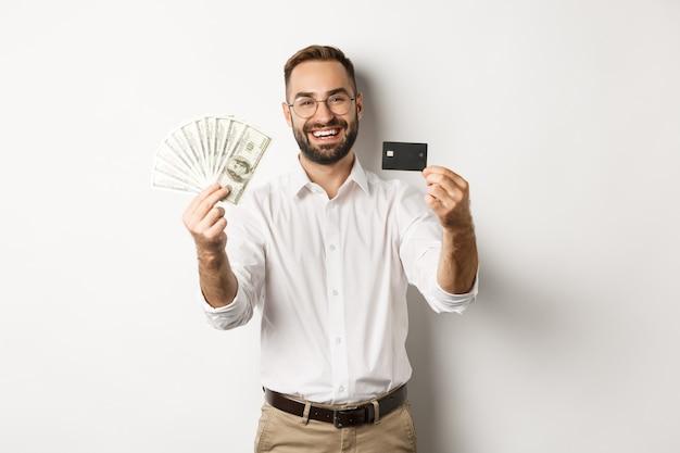 Felice giovane che mostra la sua carta di credito e denaro dollari, sorridendo soddisfatto, in piedi su sfondo bianco.