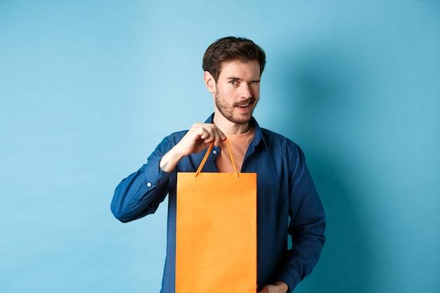 Felice giovane che mostra il sacchetto della spesa arancione e ammiccante, consigliando sconti negozio, in piedi su sfondo blu.