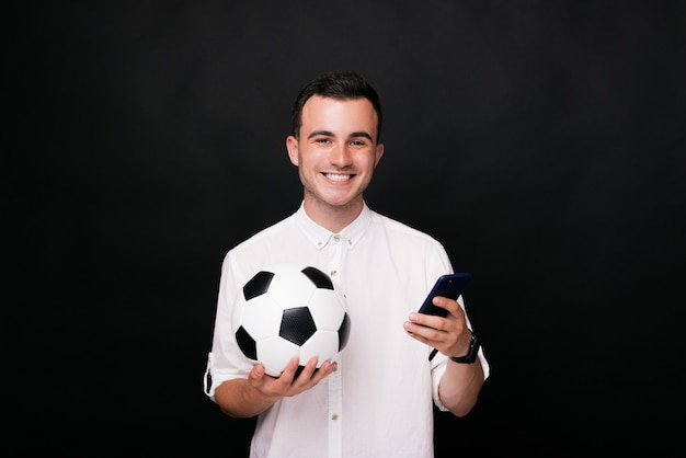 Giovane felice che sorride alla macchina fotografica che tiene il suo smart phone e un pallone da calcio su fondo nero. guardiamo la partita online al telefono!