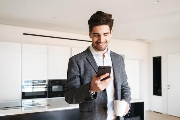 Felice giovane uomo in tuta guardando il telefono cellulare