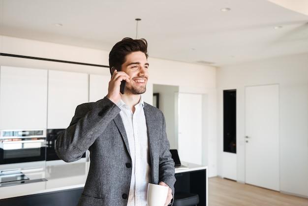 Felice giovane uomo in tuta parlando al telefono cellulare