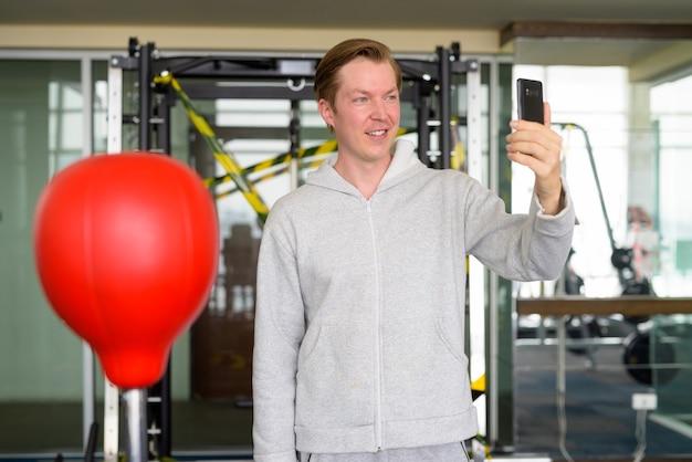 Felice giovane uomo prendendo selfie e pronto per la boxe in palestra