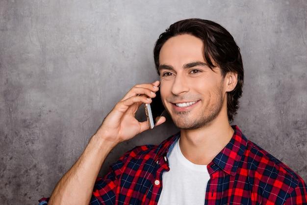 Felice giovane uomo parla cellulare e sorridente