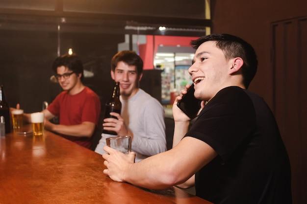 Un giovane felice che parla al telefono mentre i suoi amici si godono una birra e ridono al bar.