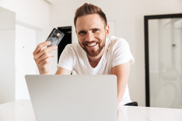 Felice giovane uomo utilizzando il computer portatile in possesso di carta di credito