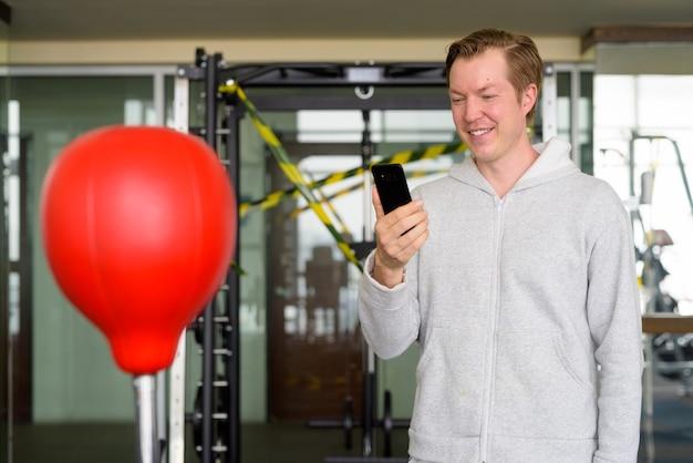Felice giovane uomo utilizzando il telefono e pronto per la boxe in palestra