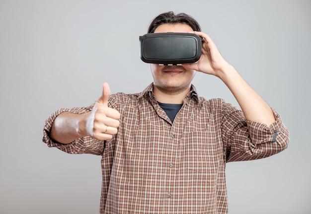 Giovane felice che usando le cuffie da realtà virtuale