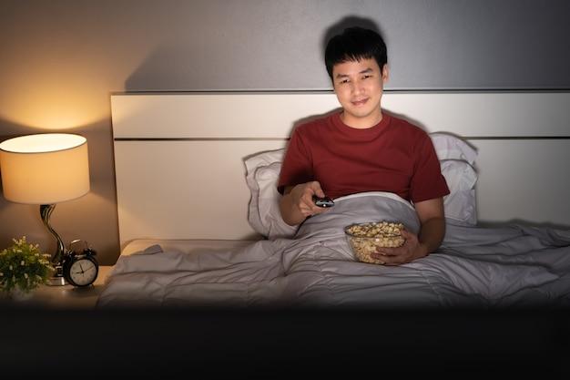 Giovane felice che guarda la tv sul letto di notte