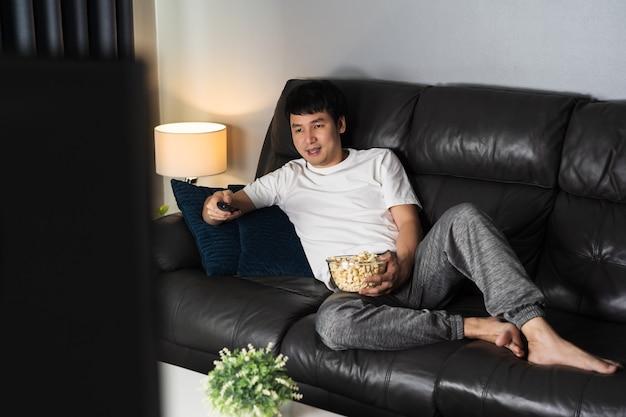 Felice giovane che guarda la tv sul divano di notte