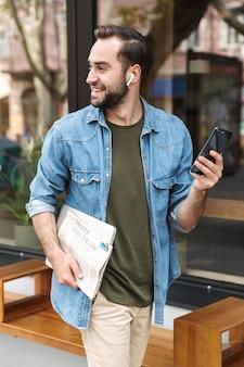Felice giovane uomo che indossa gli auricolari utilizzando lo smartphone mentre si cammina per la strada della città con giornali e laptop in mano