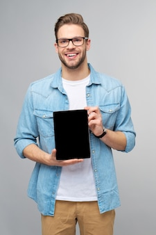 Felice giovane uomo che indossa jeans camicia in piedi e tenendo il tablet pc pad sopra studio muro grigio