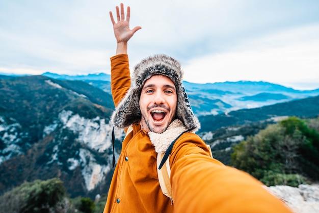 Il giovane felice con lo zaino sta prendendo un selfie sulla cima delle montagne