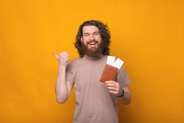 Giovane felice con la barba che tiene il passaporto con i biglietti e che punta lontano