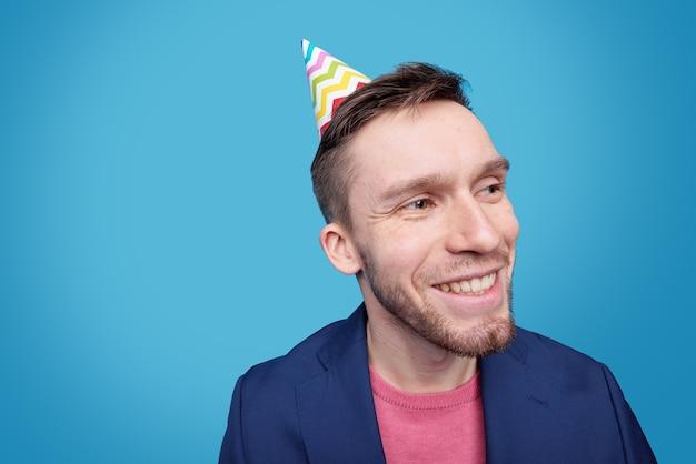 Felice giovane uomo con cappello di compleanno sulla testa guardando da parte con un sorriso a trentadue denti mentre vi godete l'evento festivo