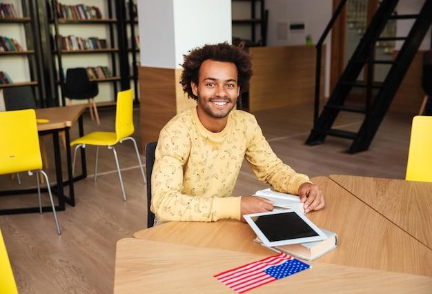 Felice giovane uomo con tablet schermo vuoto seduto e leggendo il libro in biblioteca