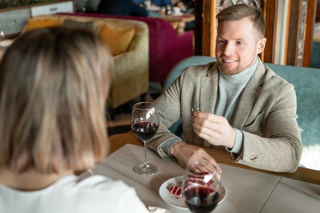 Felice giovane uomo con anello di fidanzamento che fa proposta alla sua ragazza seduta davanti a lui a tavola durante una cena romantica