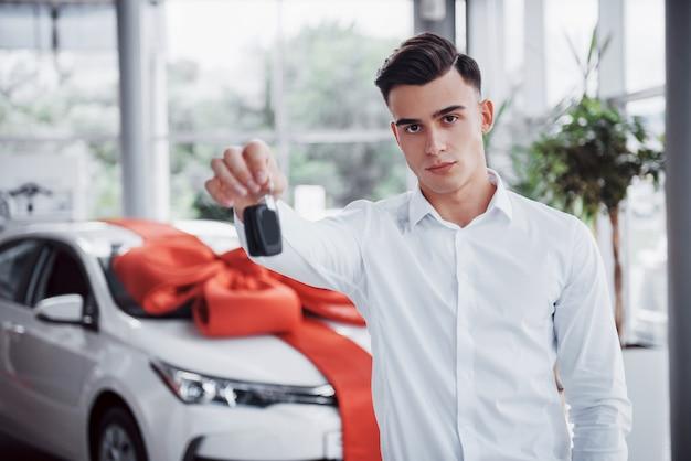 Felice giovane con le chiavi in mano, fortunato comprare una macchina