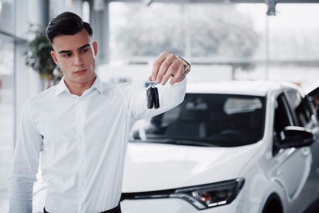 Felice giovane uomo con le chiavi in mano, fortunato acquista una macchina.