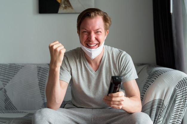 Felice giovane uomo con maschera guardando la tv e ricevendo buone notizie a casa in quarantena