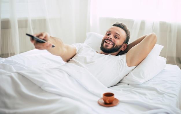Felice giovane uomo con un telecomando è sdraiato a letto e cambia canale