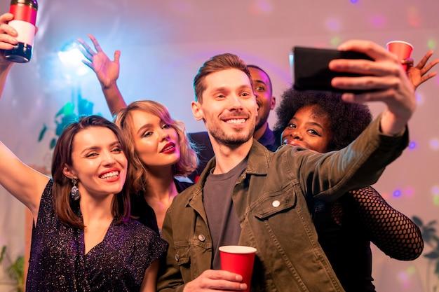 Felice giovane con smartphone e tre gioiose ragazze interculturali che fanno selfie e rallegrare con bevande a casa festa
