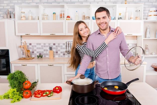 Felice giovane uomo e donna che abbraccia e cucina in cucina