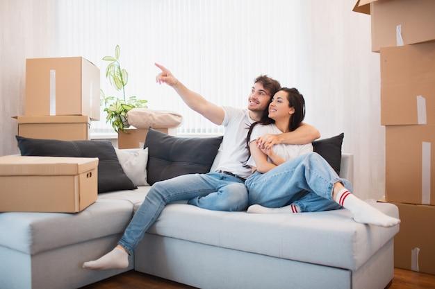 Felice giovane coppia di sposi si trasferisce nel nuovo appartamento. sono seduti sul divano e stanno guardando la loro nuova casa.
