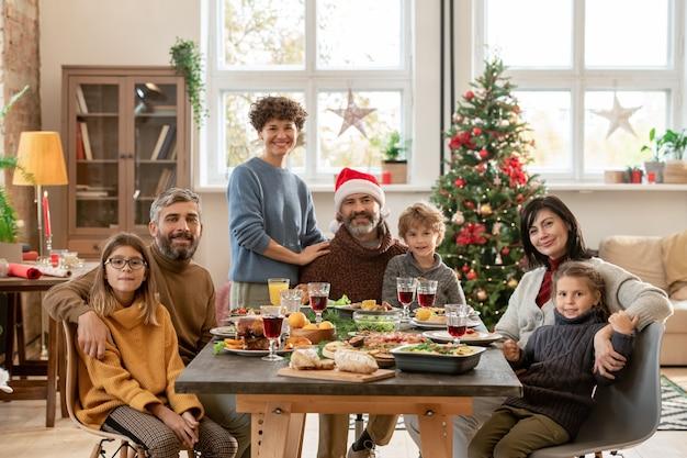 Coppie giovani e mature felici e tre bambini carini riuniti da un tavolo festivo servito per la cena di natale in soggiorno contro un albero decorato